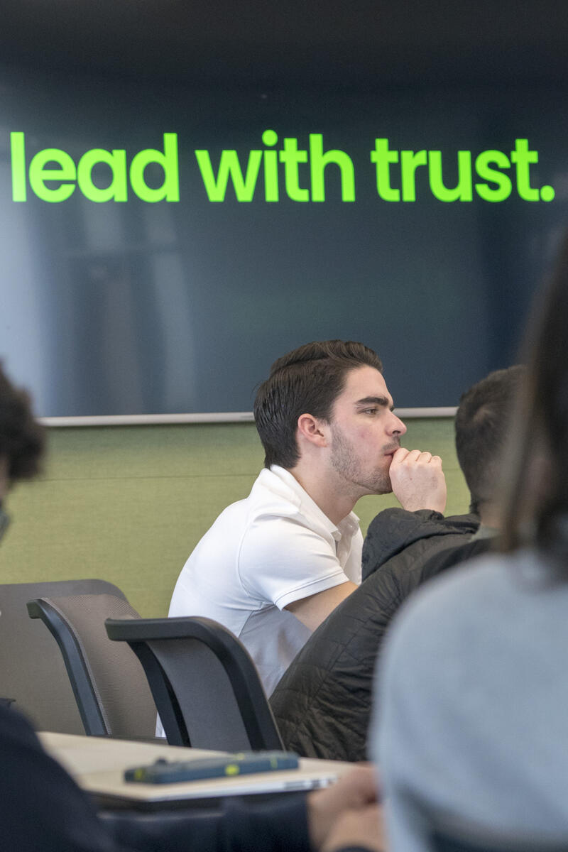 """Student listening under """"Lead with trust"""" caption"""